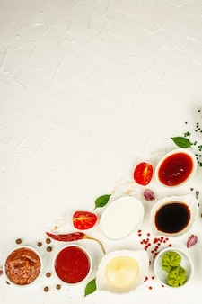 Набор различных соусов - кетчуп, майонез, шашлык, соя, чатни, васаби, аджика, хрен, айоли, маринара. белый фон шпатлевки, вид сверху