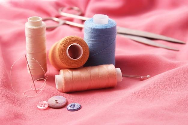 Набор различных швейных принадлежностей на цветном фоне крупным планом