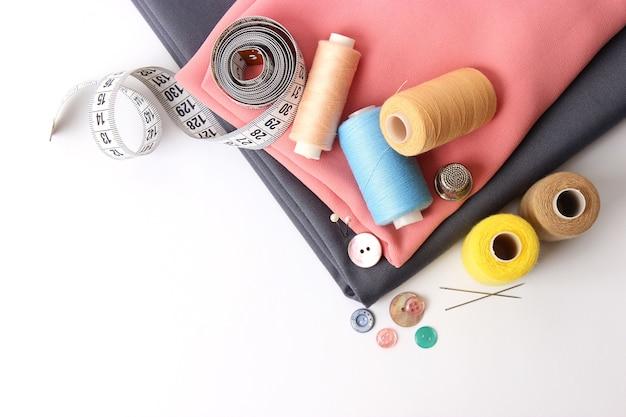 Набор различных швейных принадлежностей на белом фоне крупным планом