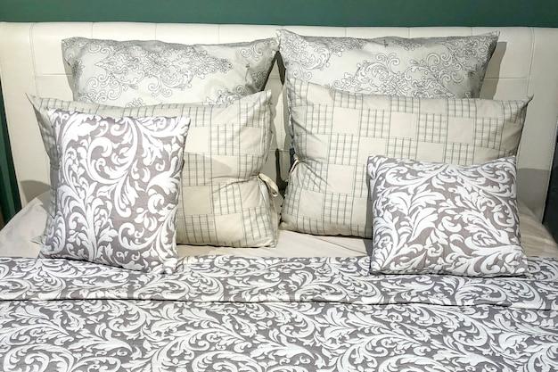 깔끔하게 정돈 된 침대에 다양한 크기의 베개 세트