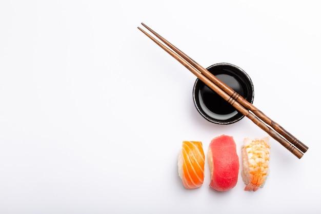 コピースペース、上面図と白い背景の上にさまざまな寿司握り、醤油、箸のセット。伝統的な日本の寿司のコンセプト、クローズアップ