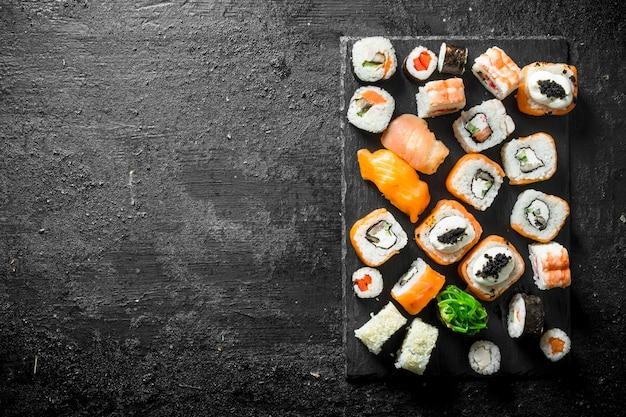 연어, 닭고기, 새우, 야채와 함께 다른 스시 롤 세트. 검은 시골 풍 테이블에