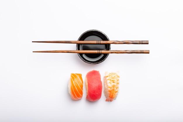 白地に鮭、マグロ、エビ、醤油、箸を使ったさまざまな寿司のセット、上面図。伝統的な日本の寿司のコンセプト、クローズアップ、フラットレイ