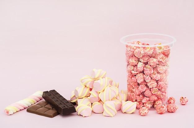 さまざまなお菓子、キャンディー、マシュマロ、チョコレート、ピンクの背景のポップコーンのセット