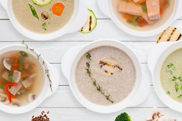 木製のテーブルにさまざまなおいしいスープのセット
