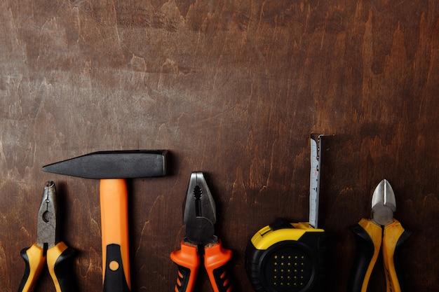 Набор различных инструментов для ремонта на деревянном фоне вид сверху
