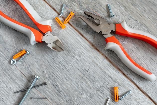 Набор различных видов плоскогубцев, боковых ножей и крепежа на сером ламинате