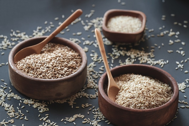Набор различных видов риса и круп в деревянных мисках и