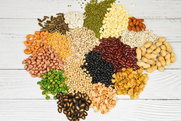 さまざまな全粒穀物豆と豆類種子レンズ豆とナッツのカラフルなスナックテクスチャ背景のセット-さまざまな豆ミックス食材の自然な健康食品のエンドウ豆農業