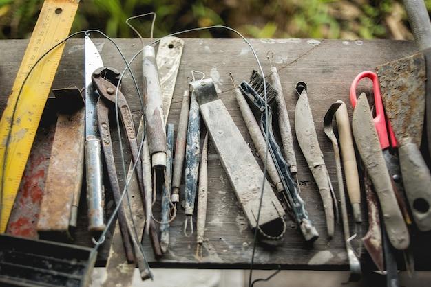 나무 테이블에 더러운 공예 조각 도구 세트
