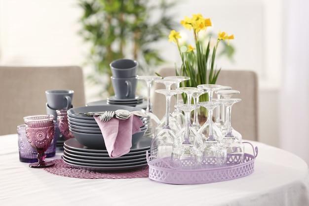 Набор посуды с сиреневыми аксессуарами на столе в ресторане