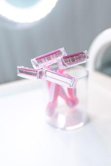 유리에 일회용 분홍색 여성 면도기 세트