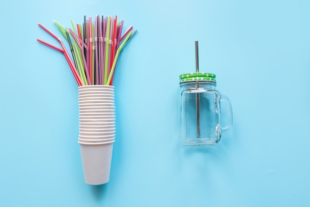 Набор одноразовых белых чашек еженедельного использования и противовеса многоразового масона для напитков ежедневного употребления на синем