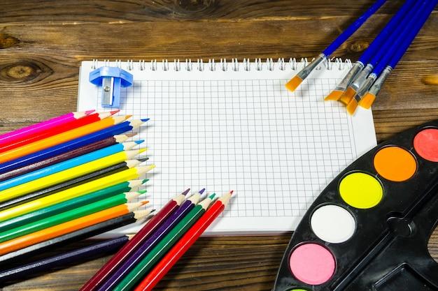 Набор инструментов для рисования на деревянных фоне. пустой блокнот, акварельные краски, кисти, цветные карандаши на столе