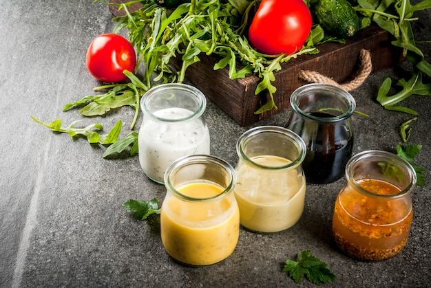 サラダ用ドレッシングのセット:ソースビネグレット、マスタード、マヨネーズまたは牧場、バルサミコ酢または大豆、バジルとヨーグルト。暗い石のテーブル。緑の野菜、サラダ用野菜。
