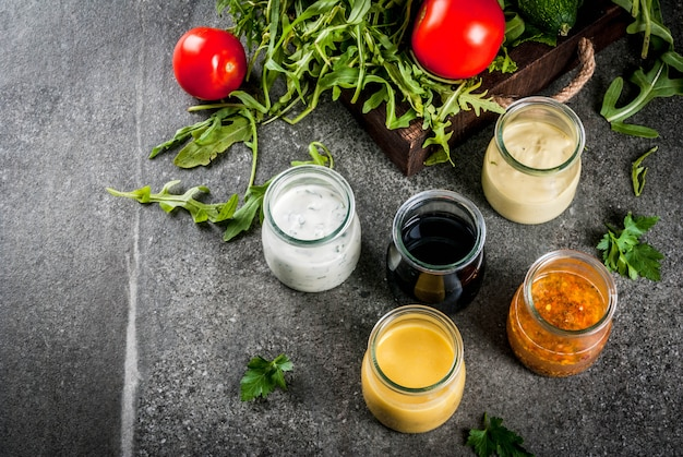 サラダ用ドレッシングのセット:ソースビネグレット、マスタード、マヨネーズまたは牧場、バルサミコ酢または大豆、バジルとヨーグルト。暗い石のテーブル。