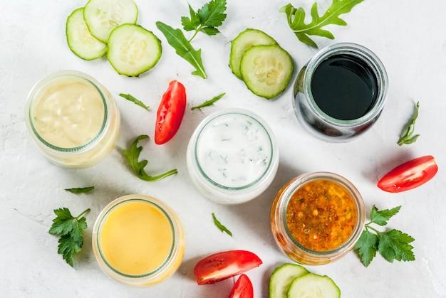 サラダ用ドレッシングのセット:ソースビネグレット、マスタード、マヨネーズまたは牧場、バルサミコ酢または大豆、バジルとヨーグルト。暗い白いコンクリートテーブル、緑、サラダ用の野菜。コピースペーストップビュー