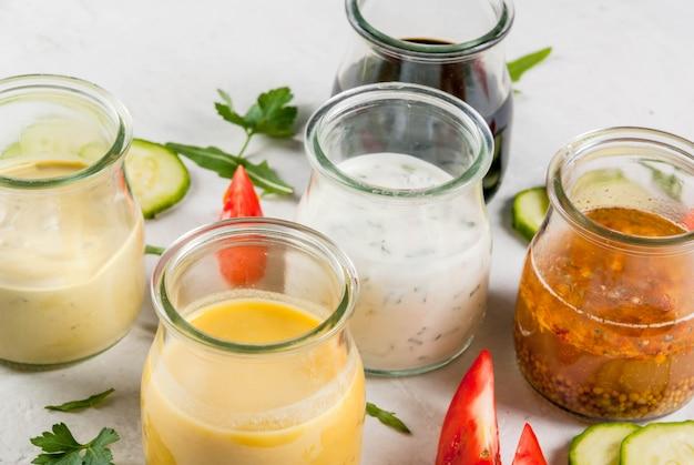 サラダ用ドレッシングのセット:ソースビネグレット、マスタード、マヨネーズまたは牧場、バルサミコ酢または大豆、バジルとヨーグルト。暗い白いコンクリートテーブル、緑、サラダ用の野菜。コピースペース