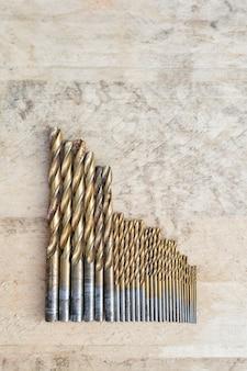 木製の背景に異なるサイズのドリルのセットです。上面図