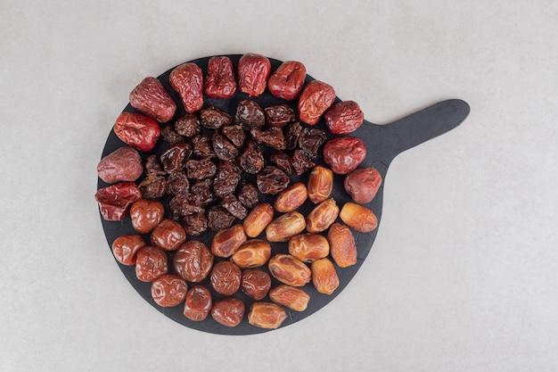 Набор сухофруктов на деревянном блюде.