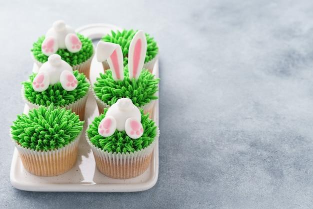子供のためのイースターカップケーキのセット。草、バニーの耳とお尻。
