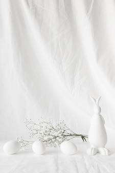 Набор пасхальных яиц возле веточек растений и фигуры кролика