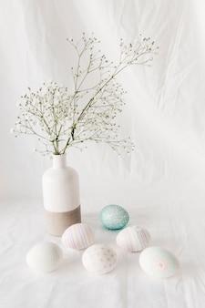 Набор пасхальных яиц с узорами возле веточки растения в вазе