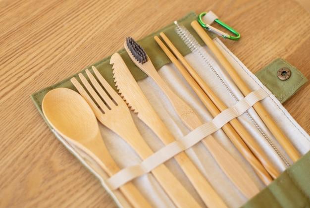 木製のテーブルにエコフレンドリーな竹カトラリーのセット。持続可能なライフスタイル。プラスチックの無料コンセプト。クローズアップ、トップビュー。