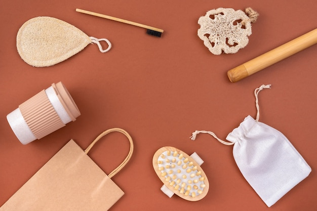 Набор из экологически чистой бамбуковой зубной щетки, эко-сумки из крафт-бумаги, многоразовой кофейной кружки, массажера, губки из люфы на коричневой поверхности. устойчивый образ жизни.