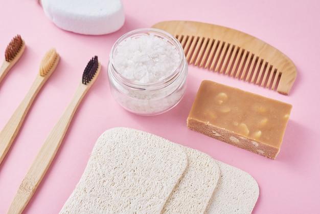 Набор экологически чистых предметов личной гигиены на розовой поверхности. бамбуковая зубная щетка, деревянная расческа, губка, мыло и морская соль, вид сверху, плоская планировка. ноль отходов концепция