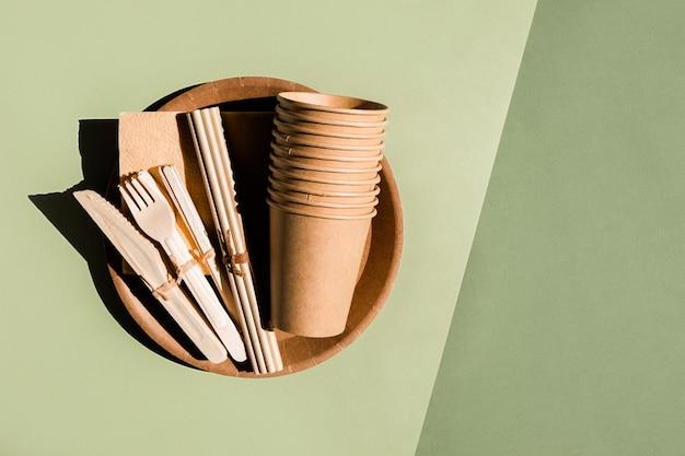 緑の背景のプラスチックフリーゼロ廃棄物コンセプトの家庭やピクニックのための環境に優しい食器のセット...
