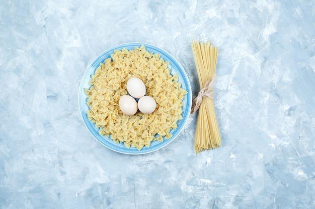 石膏の背景のプレートに卵、スパゲッティ、ファルファッレパスタのセット。フラットレイ。