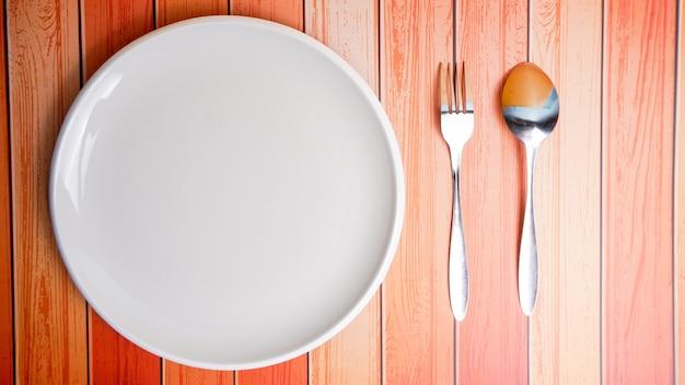 空のセラミック皿(プレート)、スプーン、木製の背景で隔離のフォークのセットです。フラットレイ、上面図。ミニマルなスタイル。