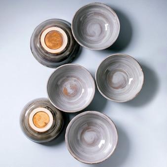 空のクラフトセラミックボウルのセットは、灰色の表面を灰色のテクスチャ釉薬で覆います