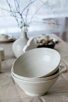 리넨 식탁보와 부활절 장식 테이블에 서있는 빈 공예 흰색 세라믹 그릇의 집합입니다.