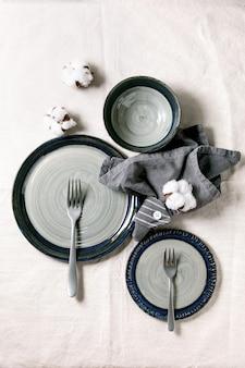 Набор пустых серых керамических тарелок с вилками и текстильной салфеткой