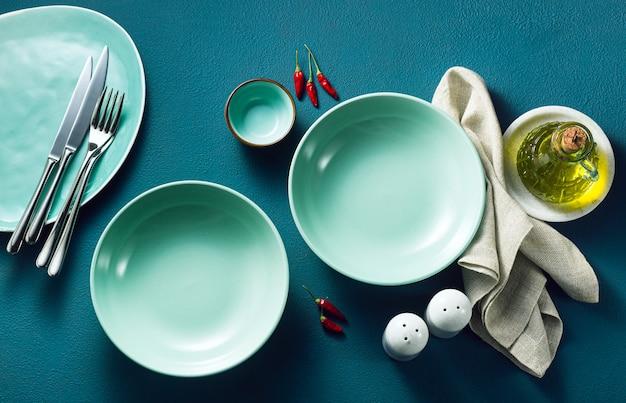Набор пустых тарелок на синем столе.