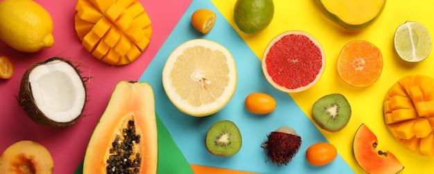 Набор экзотических фруктов на разноцветном фоне.