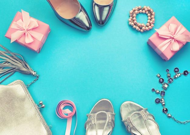 Набор модных аксессуаров плоских лежал обувь серебристого цвета на синем фоне