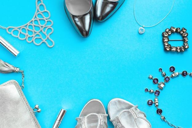 Набор модных аксессуаров плоской планировки серебристого цвета на синем фоне