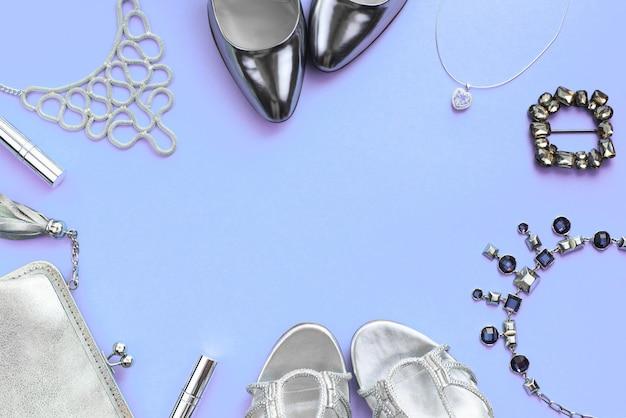 Набор модных аксессуаров плоской планировки серебристого цвета на фиолетовом фоне