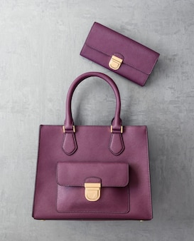 Набор модных женских сумочек на серой оштукатуренной поверхности, вид сверху