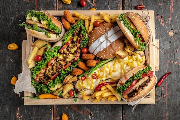 나무 테이블에 패스트 푸드 식사 핫도그, 햄버거, 감자 튀김 세트. 패스트 푸드 간식. 평면도.