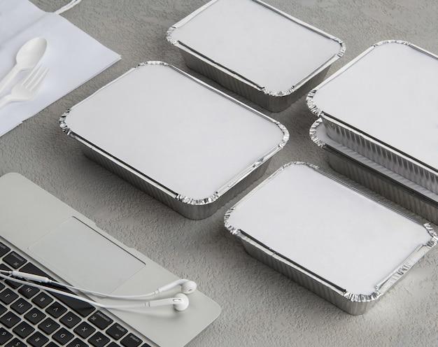 회색 배경에 노트북이 있는 패스트푸드 세트. 사업가와 바쁜 사람들을 위한 음식