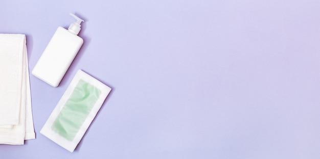 脱毛の女性のセットワックスストリップボディモイスチャライザーと白い綿タオル