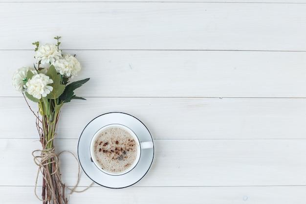 Набор цветов и кофе в чашке на деревянном фоне. вид сверху.