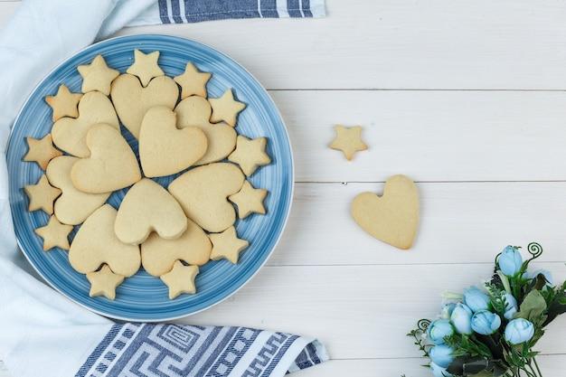 木製とキッチンタオルの背景のプレートに花とクッキーのセットです。フラットレイ。
