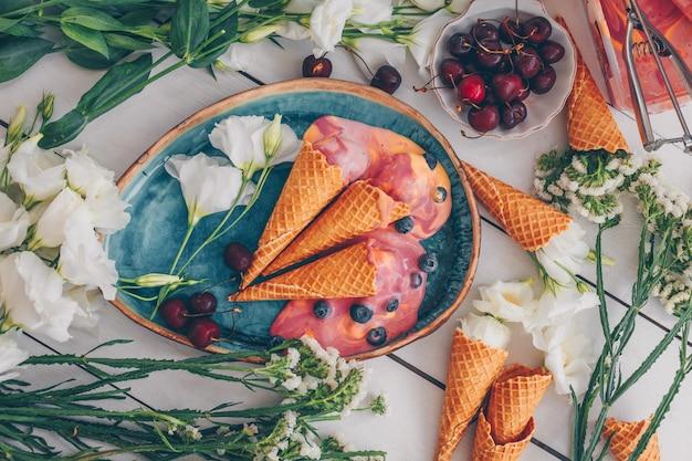 花、果物、白い木の青い皿にアイスクリームのセット。上面図。