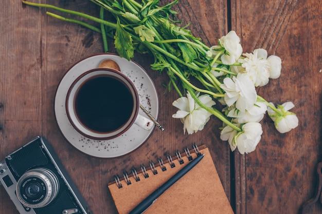 花、メモ帳、ペン、木の上のビンテージカメランコーヒーのセット。上面図。