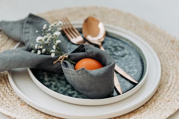 フォークとスプーンと皿に卵とトリベットと白の布のセット。ハイアングル。